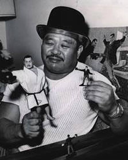 Rare photo of Harold Sakata, holding his figures